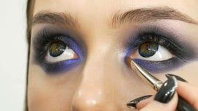 Unga härliga sexiga flickamodeller gör blå afton att utgöra rökiga ögon och med falska ögonfrans Ögon med mång--färgat stock video