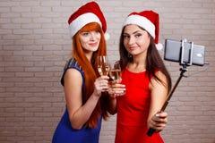 Unga härliga sexiga kvinnor i jultomtenlock med exponeringsglas av champag Arkivfoton