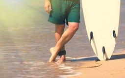 Unga härliga surfaremän på stranden med bränningbrädet på dagen bryter Royaltyfria Bilder
