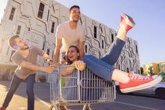 Unga härliga vänner som omkring bedrar med en shoppingspårvagn Arkivbilder