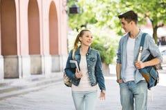 Unga högskolavänner som talar, medan gå på universitetsområdet royaltyfri foto