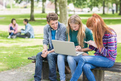 Unga högskolestudenter som använder bärbara datorn parkerar in royaltyfri fotografi