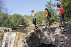 Unga handelsresande, fotvandrare nära en vattenfall Arkivfoton