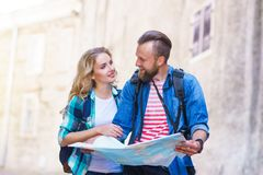 Unga handelsresande med en turist- ?versikt Man och kvinna som har semester Fotvandrare-, resa och turismbegrepp royaltyfri foto