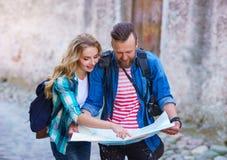 Unga handelsresande med en turist- ?versikt Man och kvinna som har semester Fotvandrare-, resa och turismbegrepp fotografering för bildbyråer