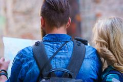 Unga handelsresande med en turist- ?versikt Man och kvinna som har semester Fotvandrare-, resa och turismbegrepp arkivbilder