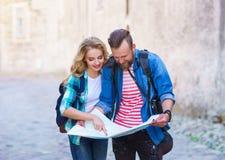 Unga handelsresande med en turist- ?versikt Man och kvinna som har semester Fotvandrare-, resa och turismbegrepp royaltyfria bilder