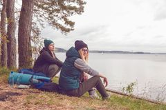 Unga handelsresandekvinnor som vilar under resande nära sjön arkivfoto