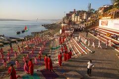 Unga hinduiska munkar för en ceremoni för att möta gryningen på banker av Ganges och lyfter den indiska flaggan royaltyfri bild