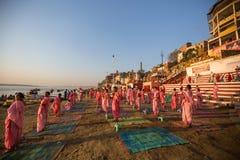 Unga hinduiska munkar för en ceremoni för att möta gryningen på bankerna av Gangesen och lyfter den indiska flaggan arkivfoto