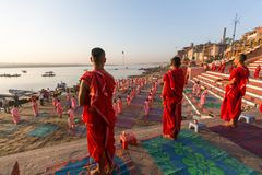 Unga hinduiska munkar för en ceremoni för att möta gryningen på bankerna av Gangesen och lyfter den indiska flaggan arkivfoton