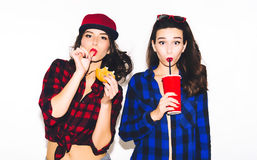 Unga hipsterflickor som har gyckel som dricker en sodavatten från sugrör och innehav en hamburgare, ett lyckligt leende och ett s arkivfoto