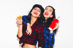 Unga hipsterflickor som har gyckel som dricker en sodavatten från sugrör och innehav en hamburgare, ett lyckligt leende och ett s arkivbild