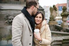 Unga hipsterpar med kaffe som kysser och att krama i gammal stad Arkivbild