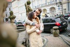 Unga hipsterpar med kaffe som kysser och att krama i gammal stad Fotografering för Bildbyråer