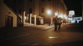 Unga hipsterpar som kramar och att gå i stadsmitten i aftonen Man och kvinna som har gyckel tillsammans stock video