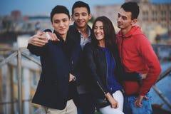 Unga hipsterpojkar och flicka som poserar, medan fotografera sig på den digitala kameran för mobiltelefonen för social nätverksbi Arkivbilder