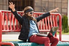 Unga hipsters med datoren sitter på en bänk Fotografering för Bildbyråer