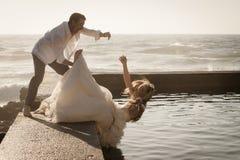 Unga härliga brud- par som har gyckel tillsammans på stranden Royaltyfri Bild