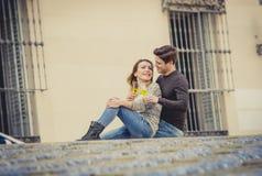 Unga härliga par som är förälskade på gatan som firar tillsammans valentindag med Champagnerostat bröd Arkivbild