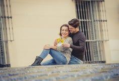 Unga härliga par som är förälskade på gatan som firar tillsammans valentindag med Champagnerostat bröd Royaltyfri Fotografi