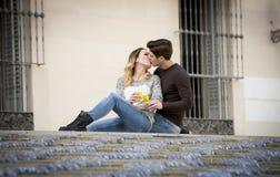 Unga härliga par som är förälskade på gatan som firar tillsammans valentindag med Champagnerostat bröd Royaltyfri Bild