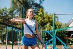 Unga idrotts- kvinnaövningar med en elastisk musikband Kondition sport fotografering för bildbyråer
