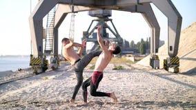 Unga idrotts- män med kala nakna torso som slåss, en manstryk, de andra nedgångarna på hans baksida, på sanden En strand stock video