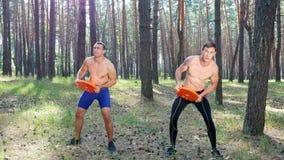 Unga idrotts- män, med kala nakna torso, utför styrkaövningar med tungviktplattor, beståndsdel av crossfit lager videofilmer