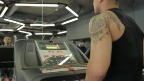 Unga idrotts- män och kvinnor som övar och kör på trampkvarnen i sportidrottshall lager videofilmer