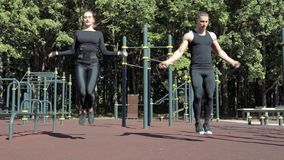 Unga idrotts- par som utomhus hoppar på överhopprepet lager videofilmer