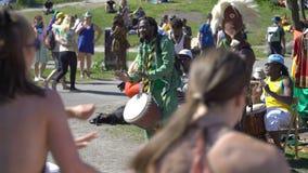 Unga infödingar av Afrika och lokalerna dansar och spelar traditionellt folk som valsar i en stad parkerar i Helsingfors stock video