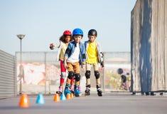 Unga inline skateboradåkare som övar på slalomkurs royaltyfria bilder
