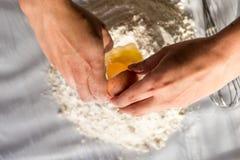 Unga italienska flickahänder som gör hemmet, gjorde italiensk pasta som bryter ägget in i mjölsikt från över royaltyfri fotografi