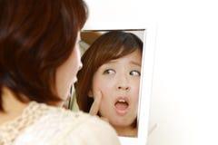 Unga japanska kvinnabekymmer om torr grov hud Arkivbild