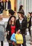 Unga japanska par med shoppingpåsen på gatan Lopp runt om Japan arkivfoto