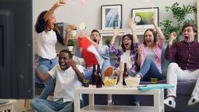 Unga kanadensare som håller ögonen på hockeyleken på TV som hurrar med att göra för flaggor som är högt-fem arkivfilmer