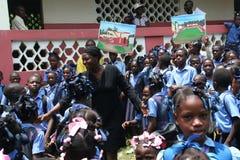 Unga katolska haitira skolbarn framme av den lantliga skolan med lärare Arkivfoton
