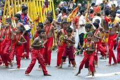 Unga Kavadi dansare flyttar sig till och med gatorna av Kandy under dagen Perahera i Sri Lanka Royaltyfri Foto