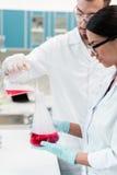 Unga kemister i glasögon och vita lag som gör experiment med agens och flaskor Royaltyfria Foton
