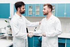 Unga kemister i vita lag som skakar händer i vetenskapligt laboratorium royaltyfri bild
