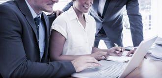 Unga kollegor som använder bärbara datorn på kontorsskrivbordet arkivfoton