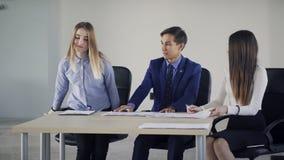 Unga kollegor som inomhus talar sammanträde på tabellen i lokal arkivfilmer