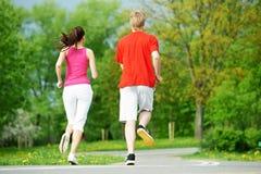 Barn bemannar och kvinnan som utomhus joggar Arkivbild