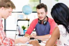 Unga kontorsarbetare eller studenter som ett lag Royaltyfri Fotografi