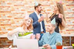 Unga kontorsarbetare firar något i kontoret arkivfoto
