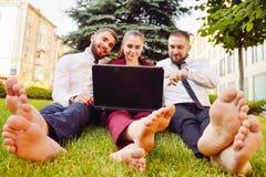 Unga kontorsarbetare med kal fot sitter på en grön gräsmatta med ett l Arkivbild