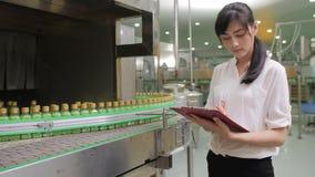 Unga kvinnliga arbetare i fabriks- bransch för drycker som kontrollerar kvaliteten av produkten stock video