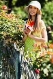 Unga kvinnliga blomsterhandlare i förklädearbete Royaltyfria Bilder