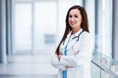 Unga kvinnliga händer för doktor Posing With Crossed på sjukhuset inomhus royaltyfria bilder